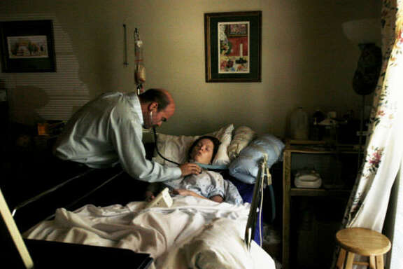 """Dr. Darcey Kobs III visits with Sarah Slusher, 22, one of his regular patients in the Houston area. """"He's been a godsend to us,"""" said Sarah's mother, Kaye Slusher. """"Before we found him we had to take her by ambulance to be treated."""" Sarah has been in a coma since an April 2006 car crash."""