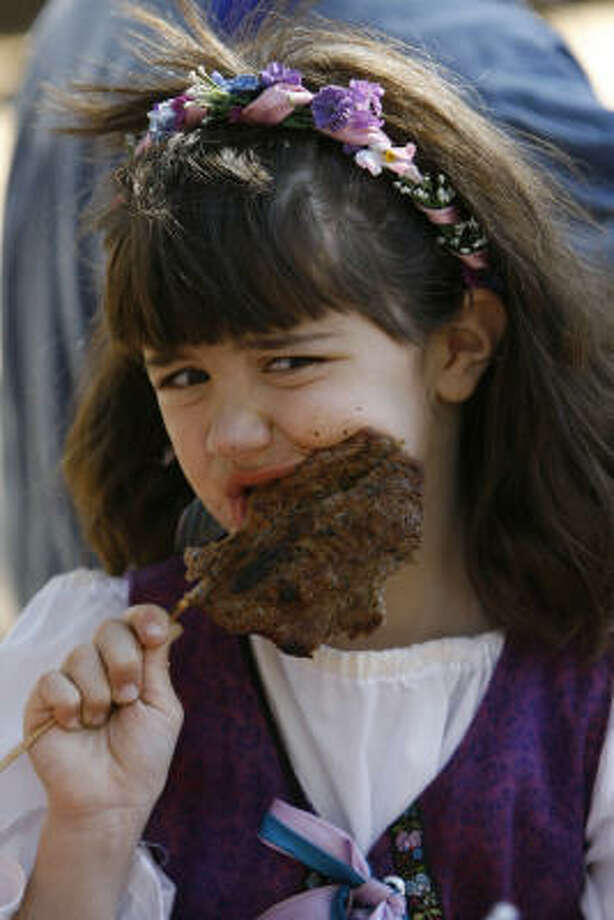 Regina Andrews, 7, of Missouri City enjoys a steak-on-a-stick during the Texas Renaissance Festival in Plantersville. Photo: Melissa Phillip, Chronicle