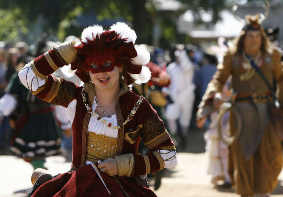 Katie Graham of Spring, dressed as Anne of Cleves, the 4th wife of Henry VIII of England, dashes to catch up to her place in the Grand Marche Parade, during the Texas Renaissance Festival Saturday. Photo: Melissa Phillip, Chronicle