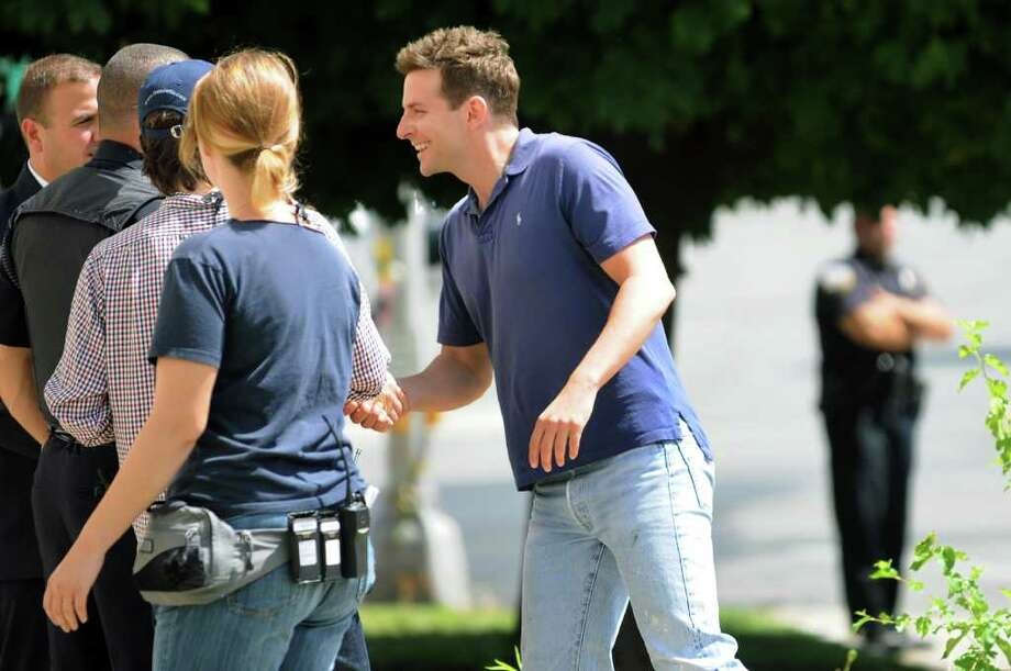 "Bradley Cooper shakes hands with police officers before entering Schenectady City Hall for the day's filming of ""The Place Beyond the Pines"" on Friday, Aug. 12, 2011, in Schenectady, N.Y. Cooper?s character is a rookie cop who eventually ascends to political power. (Cindy Schultz / Times Union archive) Photo: Cindy Schultz"