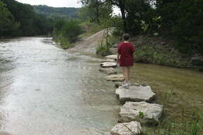 In September, after heavy rains, a walker jumps some rocks to cross a creek bed near the parking areas for the Easy and West trails.