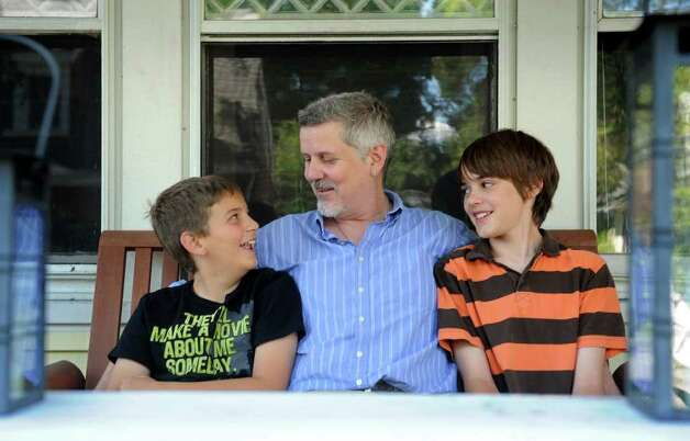 Matthew Abourezk and his sons, Zachary, 10, left, and Liam, 13, sit on the front porch of their Darien home Friday, August 12, 2011.  Abourezk has shared custody of his children and is among a growing number of single dads in Fairfield County. Photo: Autumn Driscoll / Connecticut Post