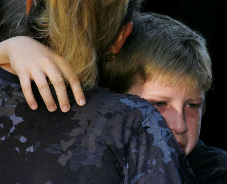 A young boy embraces a woman during a ceremony. Photo: JUSTIN LANE, Associated Press