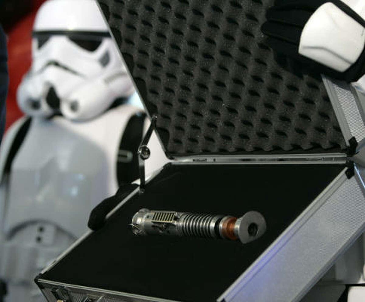 Luke Skywalker's original lightsaber is displayed by a Star Wars character.