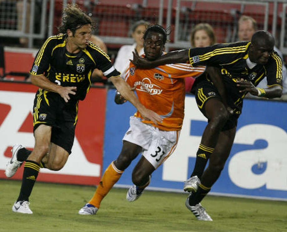 Joseph Ngwenya, center, is blocked by the Columbus Crew's Frankie Hejduk, left, and Ezra Hendrickson from chasing the play. The Dynamo extended their lead in the Western Conference to two points with a 1-1 tie. Photo: James Nielsen, Chronicle