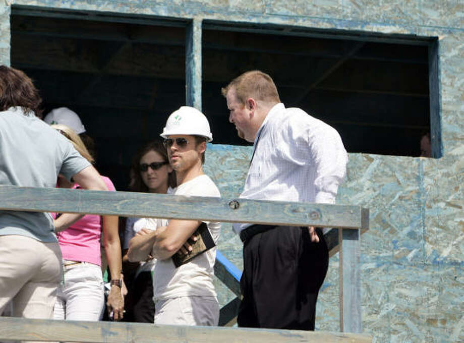 Brad Pitt, second from right, takes a tour of an environmentally friendly house under construction in the Lower Ninth Ward of New Orleans. Photo: Alex Brandon, AP