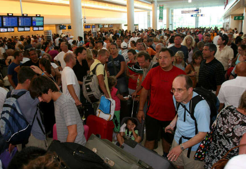 Tourists wait to depart from Cancun's international airport Aug. 19.