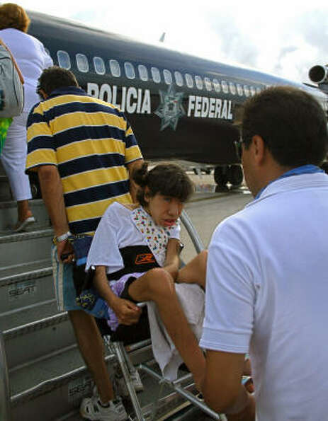 A handicapped girl is helped to board a Mexican Federal Police plane Aug. 19 during evacuations for