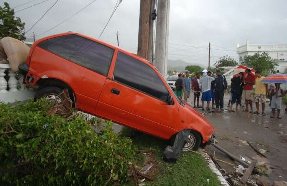 A car in Jamaica's Caribbean Heights was pushed up a wall by tidal surge Aug. 20.