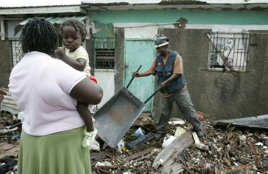 Residents of Bullbay, Jamaica, dig out homes knocked over by a tidal surge Aug. 20.