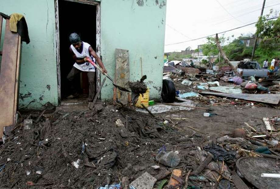 Dewin Wallis removes mud and debris from inside his Bullbay neighborhood home Aug. 20 after it was flooded and partially destroyed when Hurricane Dean passed Jamaica. Photo: Andres Leighton, Associated Press