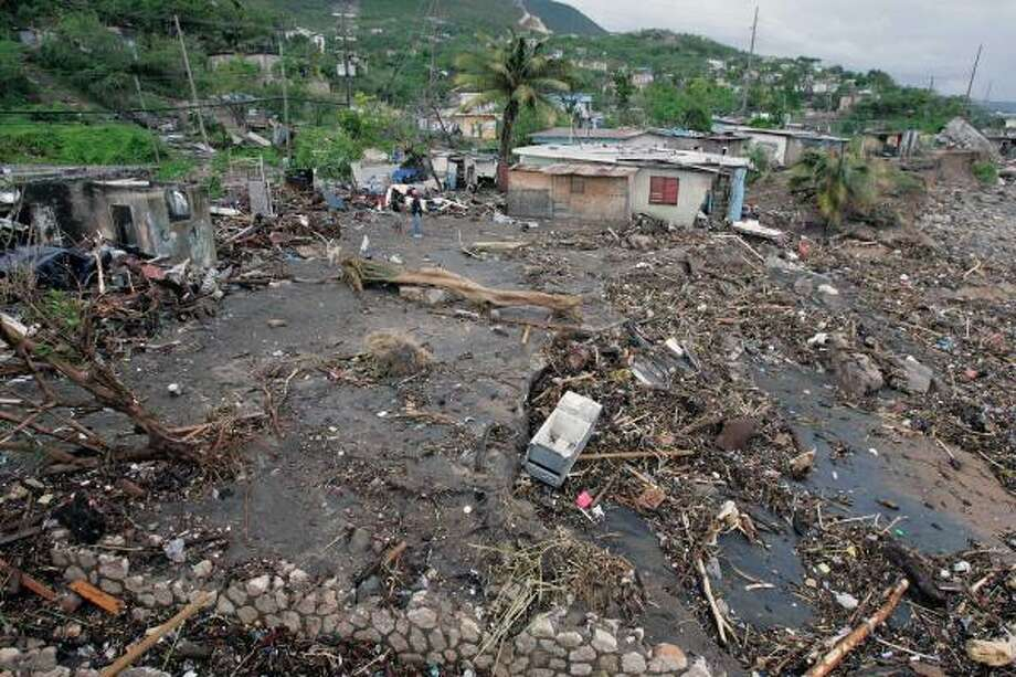 Bullbay neighborhood residents inspect the damage to their property Aug. 20. Photo: Andres Leighton, Associated Press