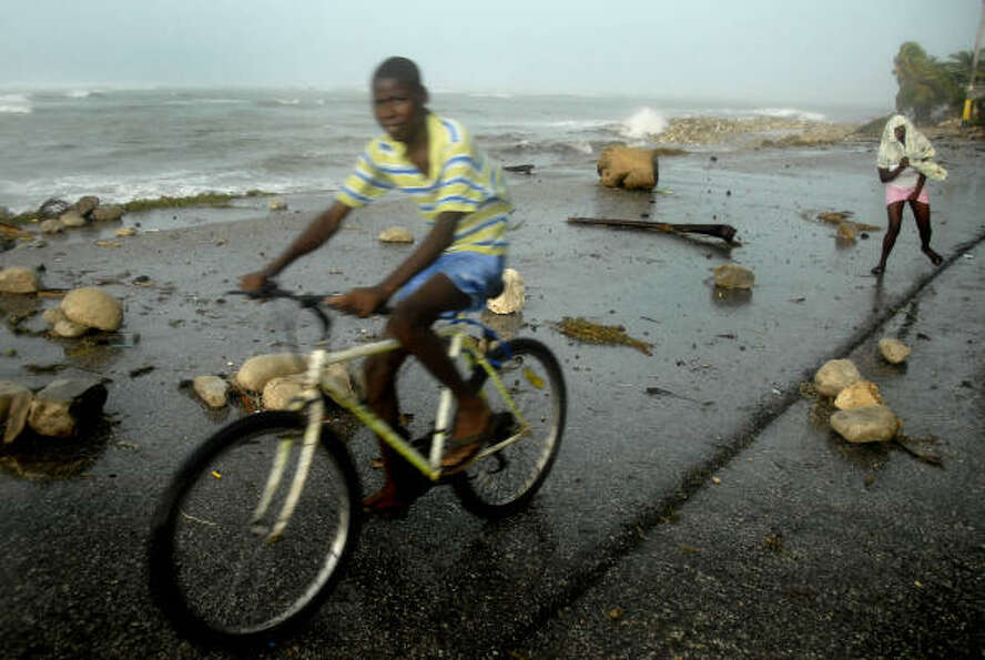 Haitians make their way around debris deposited by Hurricane Dean in Cayes-Jacmel, southeastern Hait