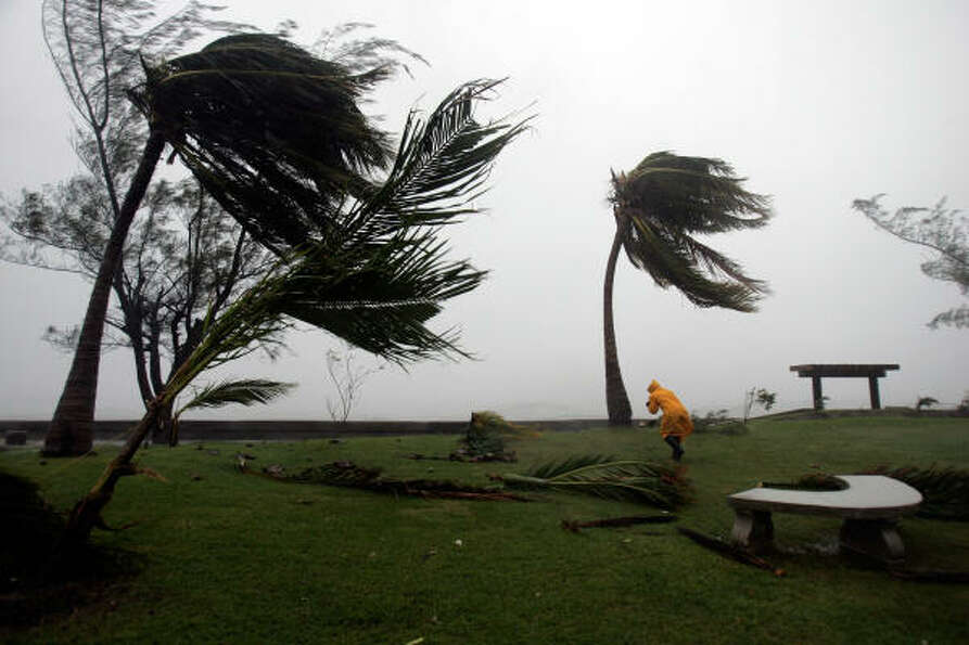 A photojournalist fights the wind to approach a waterfront boulevard in downtown Kingston as Dean po