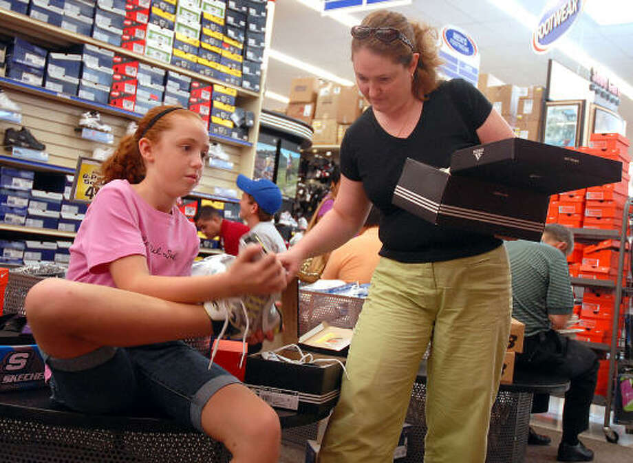 Catherine Ducote, 11, tries on shoes with her mother Elizabeth while shopping for school clothes at Academy on the Southwest Freeway during tax-free weekend Saturday. Photo: Dave Rossman, For The Chronicle