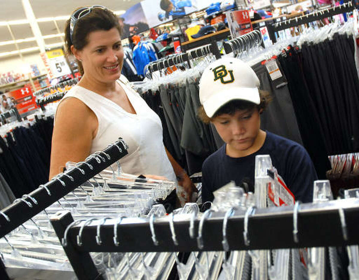 Elizabeth Bunk and her son Foley, 10, shop for school clothes at Academy on the Southwest Freeway.