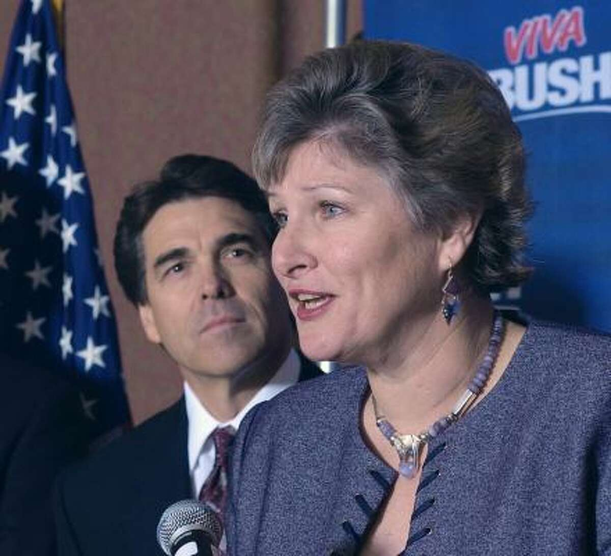 Flanked by Gov. Rick Perry, Karen Hughes, right, announces the Bush campaign's Texas leadership team during a news conference on Dec. 16, 2003.