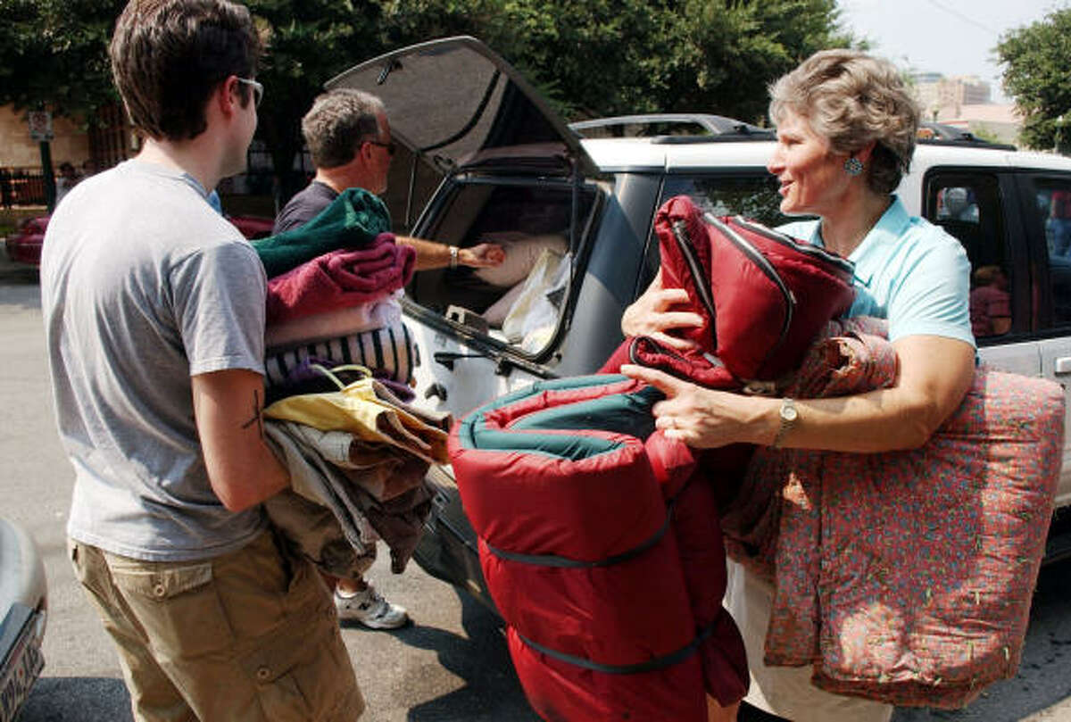 Karen Hughes, right, and John Naeve, left, take donations from Jack Nichols, center, for the Hurricane Katrina evacuees at the Austin Convention Center on Sept. 3, 2005.