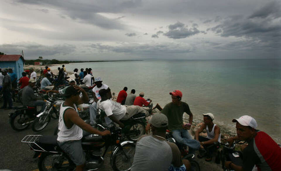 People wait for Hurricane Dean on Saturday as they look out at the Caribbean Sea from Pedernales, Do