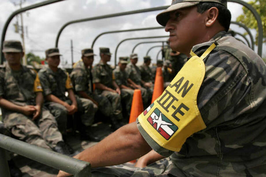 Army soldiers, wearing their National Disaster Plan 3 armband, arrive in the resort city of Cancun, Mexico in preparations for the arrival of Hurricane Dean on Friday. Photo: Israel Leal, AP