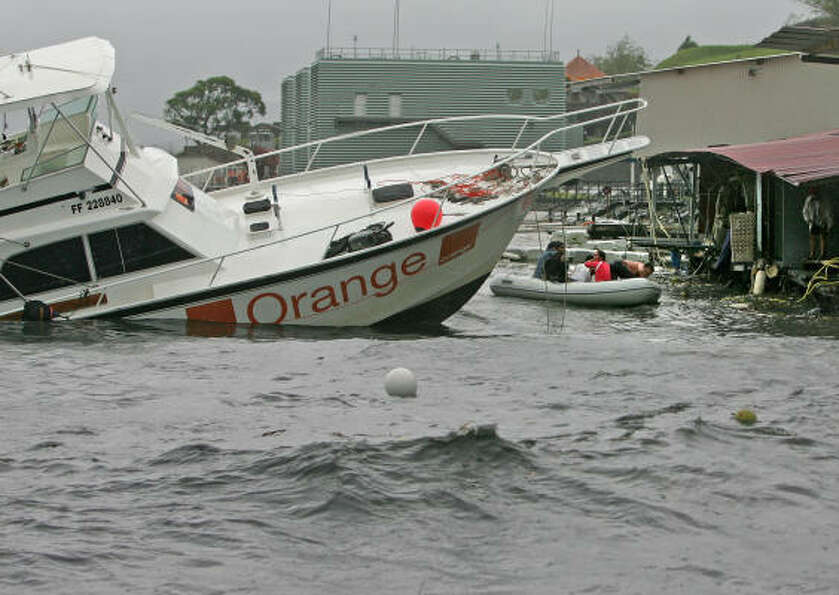 A group of boaters abandon a damaged and sinking pleasure craft in a rubber dinghy, right, after Hur