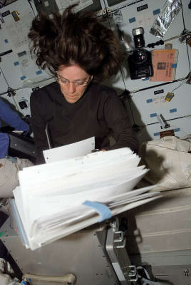 Barbara Morgan looks over procedure checklists on the middeck of Endeavour while docked with the space station Wednesday. Photo: NASA