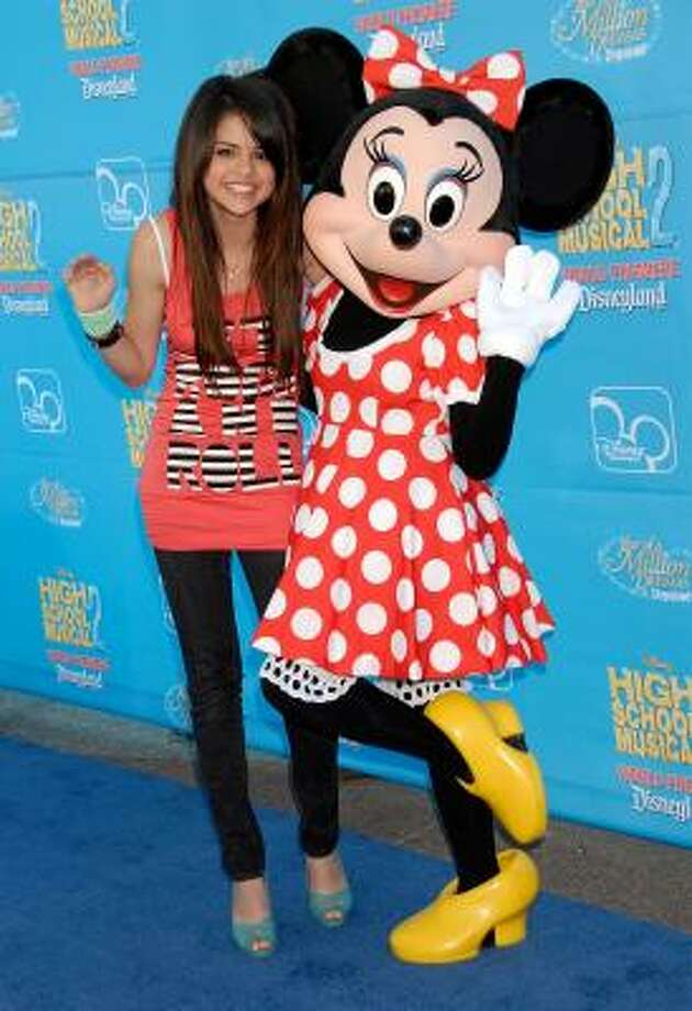 "Selena Gomez turns 24 on Friday, July 22. Let's take a look at her style since she was first boosted into stardom. Pictured: Selena Gomez poses with Minnie Mouse at the premiere of Disney Channel's ""High School Musical 2"" on Aug. 14, 2007 in Anaheim. Photo: Charley Gallay, Getty Images"