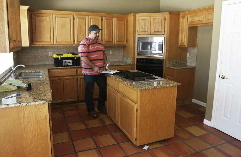 Home inspector Jeff Adams stands in the kitchen of a house for sale on Butlers   Bridge Road. He says an inspection can take anywhere from two to five hours.  Photo: SALLY FINNERAN, SAN ANTONIO EXPRESS-NEWS / sfinneran@express-news