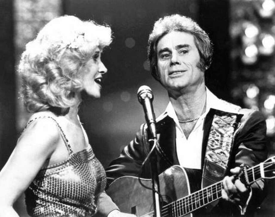 Tammy Wynette, left, sings with George Jones in an undated photo. Jones was one of Wynette's 5 husbands and a frequent singing partner. She died in 1998 at age 55. Photo: AP