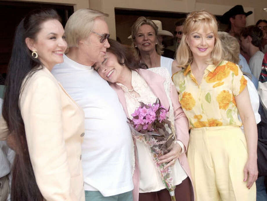 Loretta Lynn and George Jones, center, hug as they pose with Naomi Judd, right, and Crystal Gayle after cutting the ribbon to open Lynn's Coal Miner's Daughter Museum in Hurricane Mills, Tenn., on May 26, 2001. Photo: JOHN RUSSELL, AP