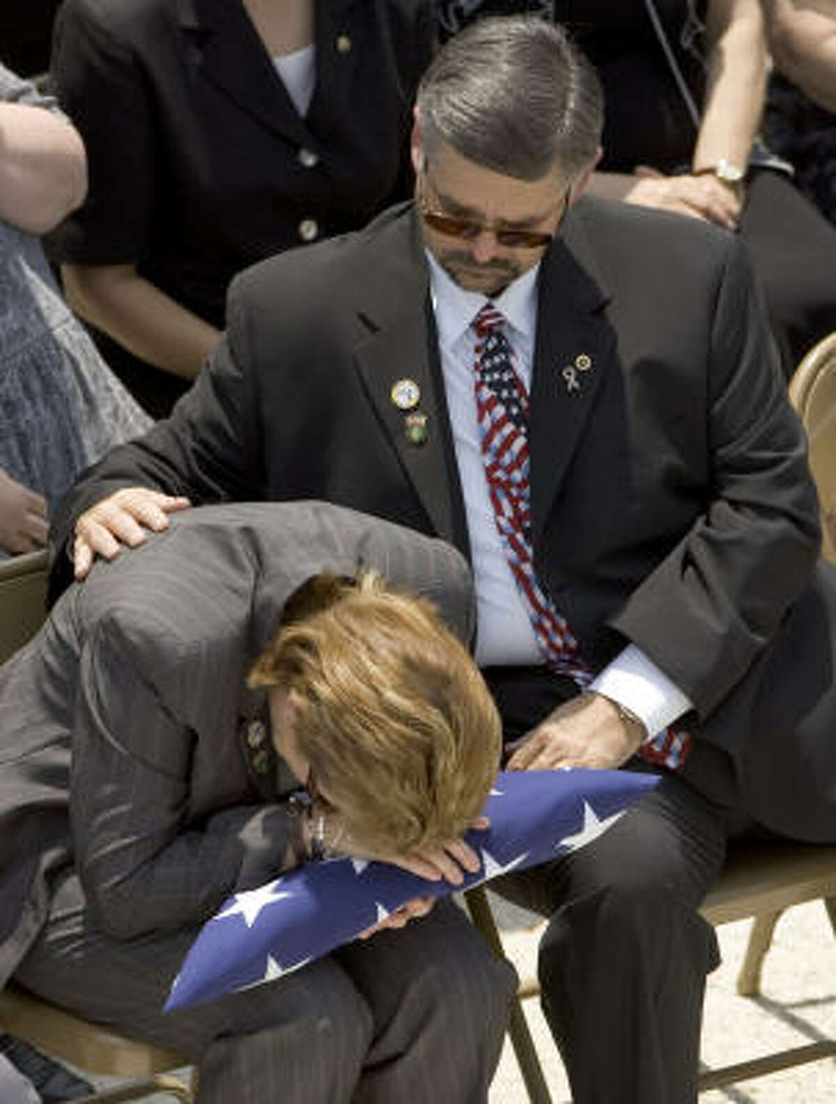 Melinda Carroll is comforted by her husband, David, as she lays her head on the flag presented to her during the funeral for her son, Cpl. Zachary Endsley, on Friday in Houston.