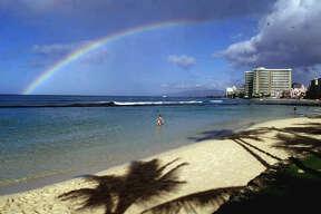 Hawaii:  A rainbow is seen over a nearly-deserted stretch of Waikiki Beach in Honolulu.