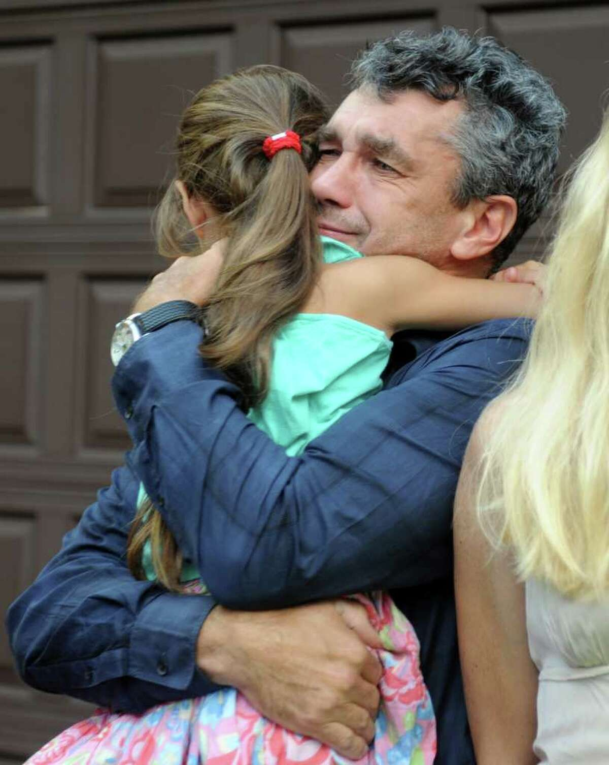 Tomasz Kocab hugs his eight-year-old daughter Zosia Friday, August 12, 2011 upon returning home to Monroe after his release from U.S. Immigration and Customs Enforcement detention in Massachusetts. Kocab was reunited with his family after being granted a six-month reprieve from deportation to Poland.