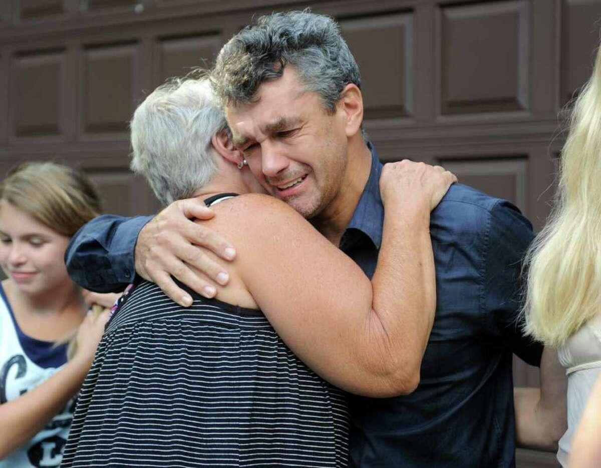 Tomasz Kocab hugs neighbor B.J. Berchem at his home in Monroe Friday, August 12, 2011 after his return from U.S. Immigration and Customs Enforcement detention in Massachusetts. Kocab was granted a six-month reprieve from deportation to Poland.