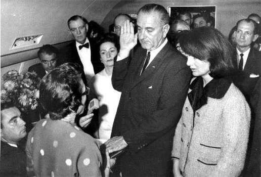 Lyndon B. Johnson takes the presidential oath of office aboard Air Force One, Nov. 22, 1963, after the assassination of JFK. Johnson is flanked by Lady Bird Johnson, left and Jacqueline Kennedy, right. Photo: Chronicle File