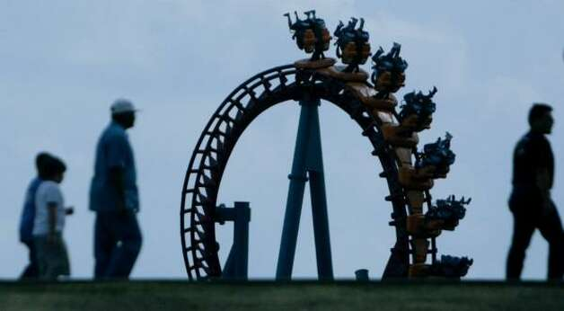 "AstroWorld attendees get a view of the ""Serial Thriller"" roller coaster as they enter the theme park on its last day on Oct. 30, 2005. Photo: Mayra Beltran, Houston Chronicle"