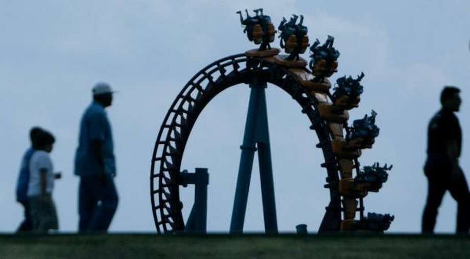 """AstroWorld attendees get a view of the """"Serial Thriller"""" roller coaster as they enter the theme park on its last day on Oct. 30, 2005. Photo: Mayra Beltran, Houston Chronicle"""