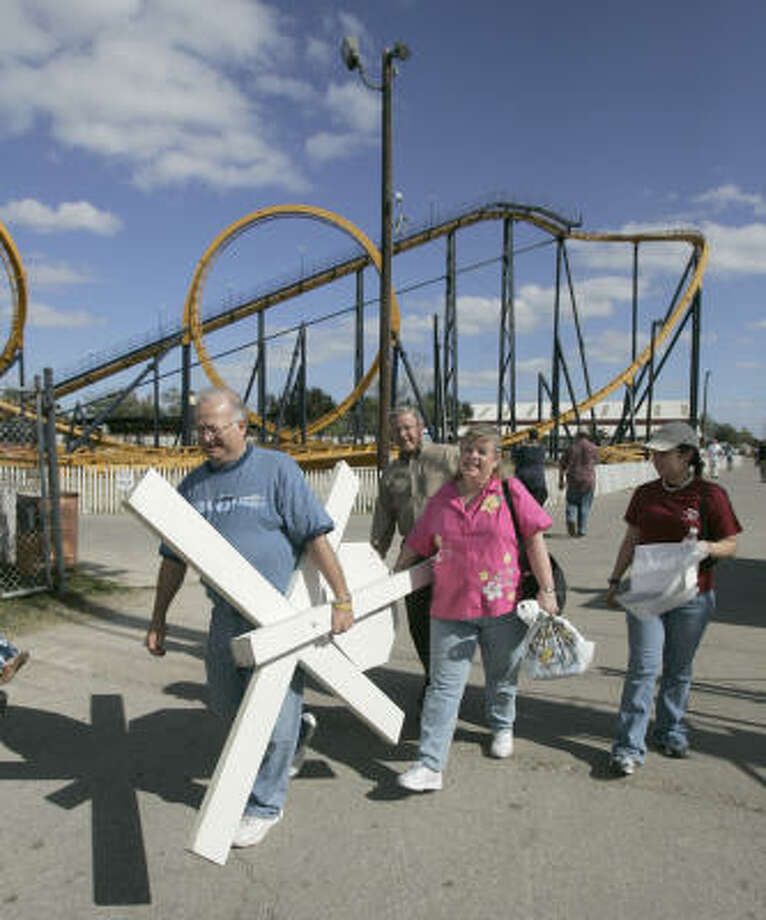 Richard Foisner, his father, Leo Foisner, his wife, Nancy Foisner, and daughter, Kelly Foisner carry a railroad crossing sign out of AstroWorld after purchasing it in the AstroWorld auction. Photo: Steve Campbell, Chronicle File
