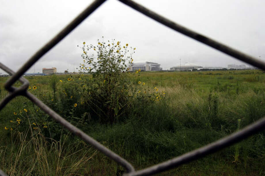 A view of the vacant lot through a surrounding gate. Photo: Johnny Hanson, For The Chronicle
