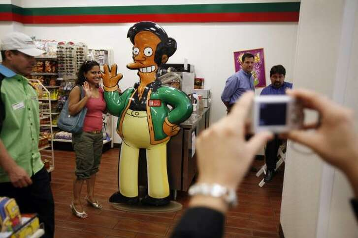 "Shelly Ramsammy poses with a representation of ""Apu,"" fictional owner of the Kwik-E-Mart from the show ""The Simpsons"" in New York City."