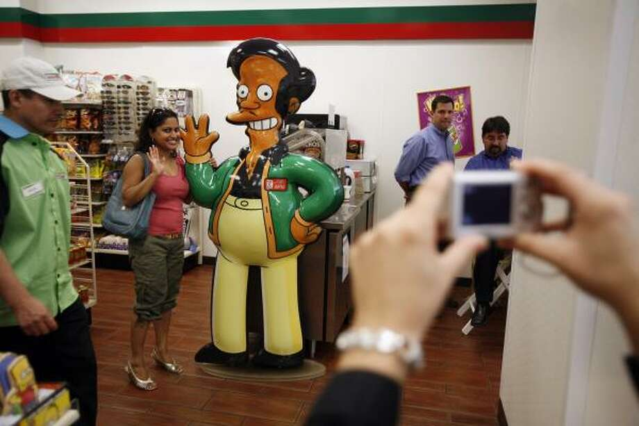 "Shelly Ramsammy poses with a representation of ""Apu,"" fictional owner of the Kwik-E-Mart from the show ""The Simpsons"" in New York City. Photo: Michael Nagle, Getty Images"