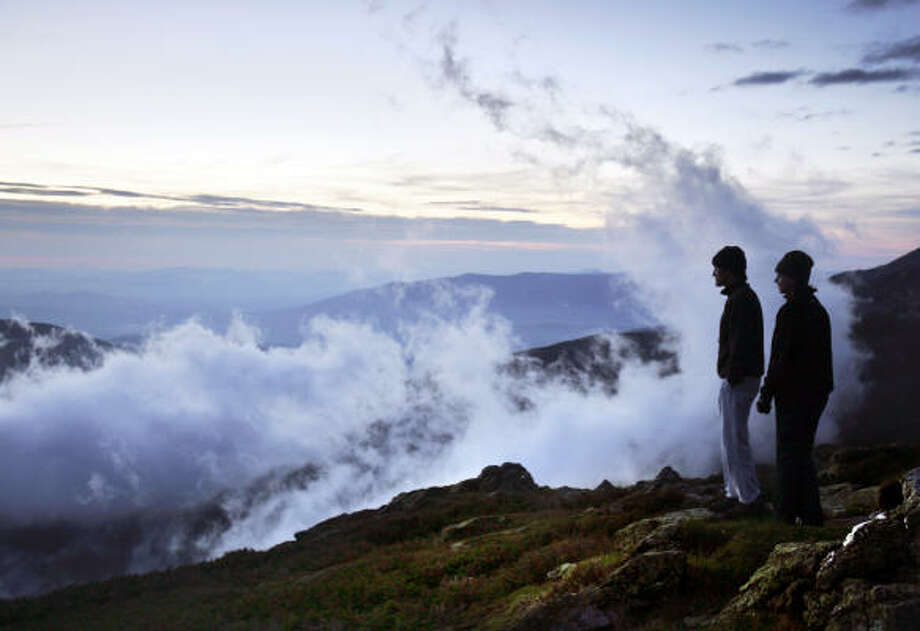 Arnaud Bewley and Abby Chiverton, of New York,  watch clouds swirl up the shoulder of Mount Washington, N.H., during twilight at the Lakes of the Clouds hut. Photo: Robert F. Bukaty, Associated Press
