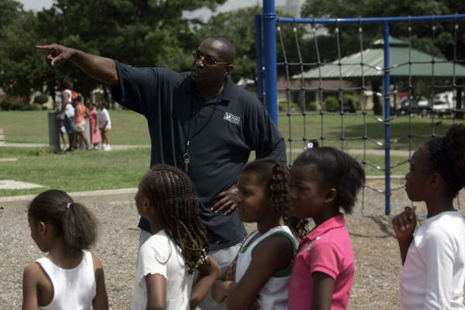 Emancipation Park Community Center facility manager Horace Chaney leads a group of children on the park's playground. Chaney said they have adopted a new curriculum that will help teach the children about the park's history. Photo: Johnny Hanson, For The Chronicle