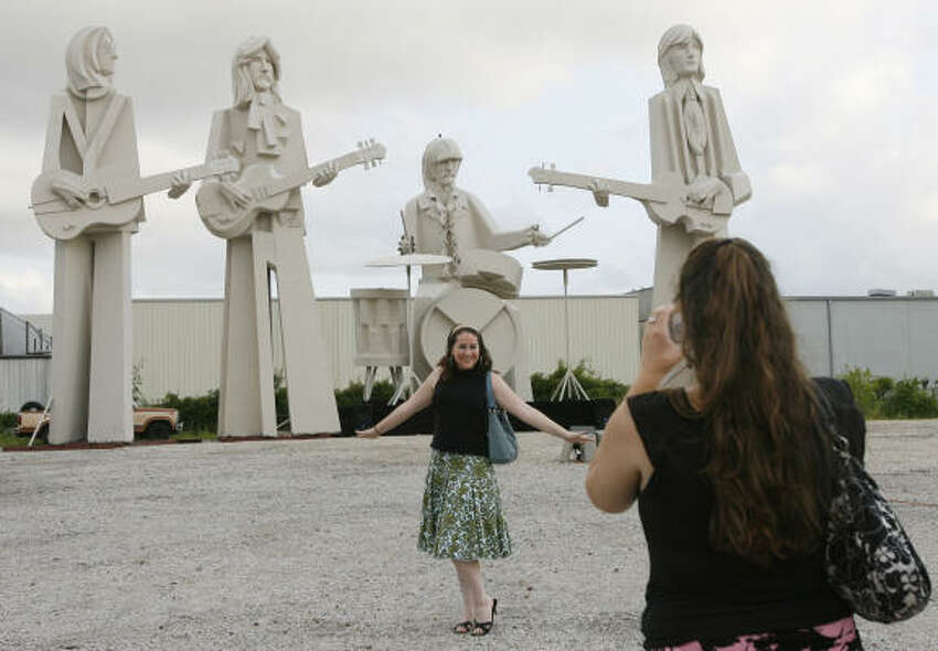 Liz Dannemiller poses for Anna Schumann in front of David Adickes' Beatles statues Thursday at his SculpturWorx Studio on Summer near Interstate 10 and Taylor.