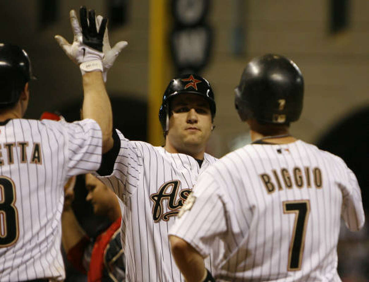 Lance Berkman, center, is greeted by Mark Loretta, left, and Craig Biggio after hitting a three run homer in the fifth inning. Loretta and Biggio scored on the homer.