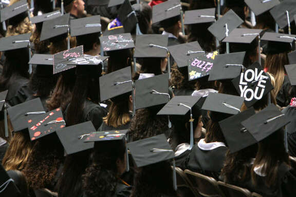 Students express emotions, biblical passages, and names on top of their graduation hats during the College of Education commencement ceremony at University of Houston in the Hoffheinz Pavilion on Saturday.