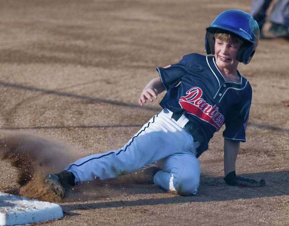 Danbury's Cody Waterbury slides into third during the 9-year-old Cal Ripken League New England Regional Championship game against Bethel at Mitchell Park in Bethel. Friday, Aug. 12, 2011 Photo: Scott Mullin / The News-Times Freelance