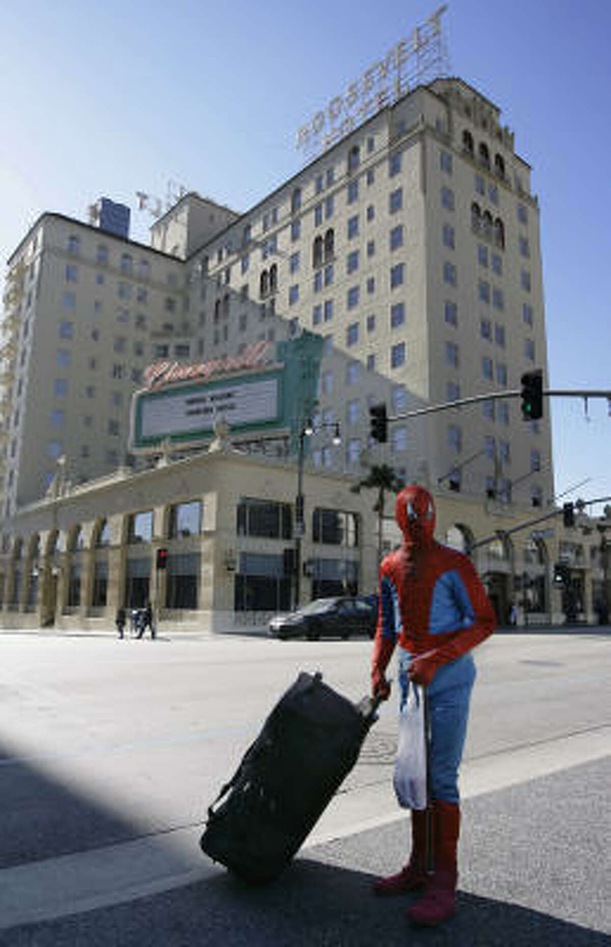 A Spiderman impersonator crosses the street with his luggage near the Roosevelt Hotel in Hollywood.