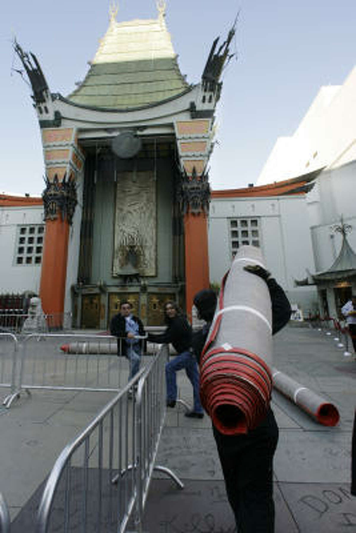 Workers haul in red carpet before a movie premiere outside the Grauman's Chinese Theatre.