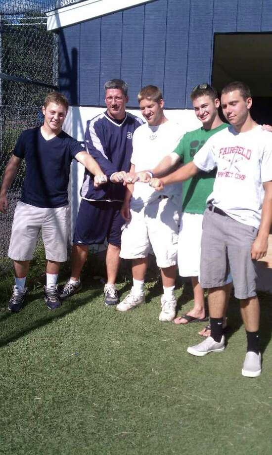 Staples baseball coach Jack McFarland, second from left, displays his 2011 FCIAC championship ring with four outgoing seniors, from left, Mike McGowan, Rob Gau, Brendan Bernstein and Chris Lametta. Photo: Contributed Photo